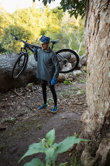 Male man mountain biker carrying bicycle in the forest