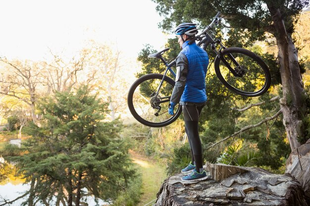 Male man mountain biker carrying bicycle looking at nature