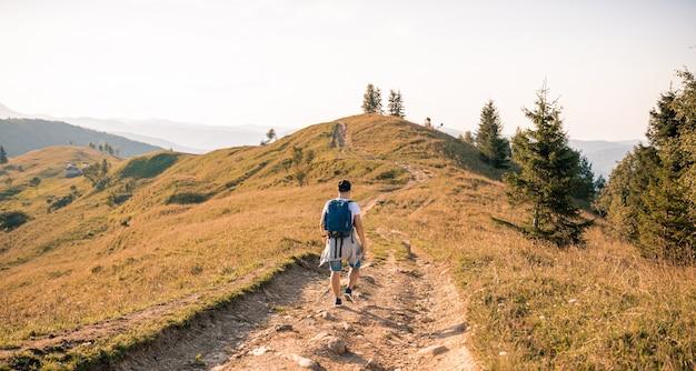 山の丘の背景に男性男性旅行者
