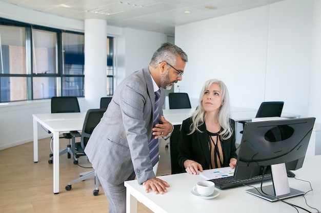 여성 상사에게 자신의 보고서를 설명하는 남성 관리자. 동료 앉아서 pc와 직장에서 서 다이어그램을 논의. 비즈니스 커뮤니케이션 개념