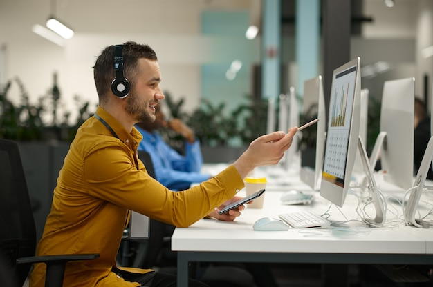 Male manager in headphones on his workplace, idea developing in it office. professional worker, planning or brainstorming. successful businessman works in modern company