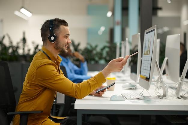 Менеджер-мужчина в наушниках на своем рабочем месте, идея развивается в ит-офисе. профессиональный работник, планирование или мозговой штурм. успешный бизнесмен работает в современной компании