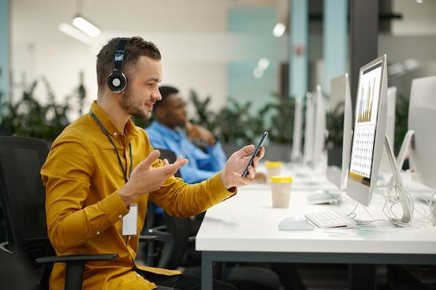 직장에서 헤드폰을 끼고 있는 남성 관리자, it 사무실에서 아이디어를 개발 중입니다. 전문 작업자, 계획 또는 브레인스토밍. 성공적인 사업가는 현대 회사에서 일합니다