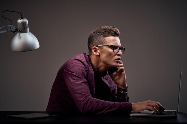 Менеджер-мужчина сидит за столом, разговаривает по телефону и использует ноутбук