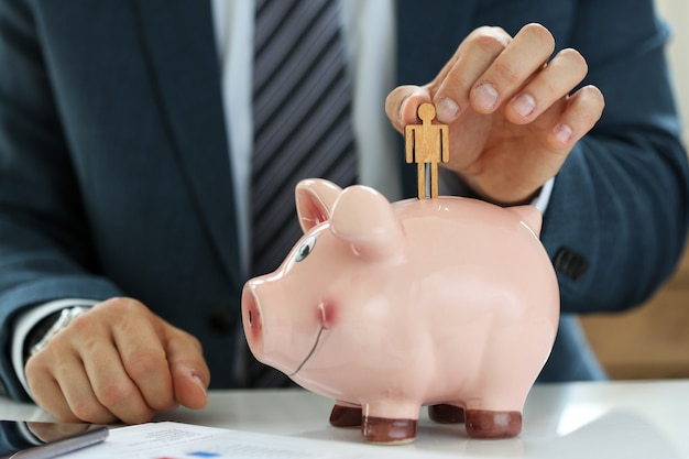 Male manager putting small wooden human figure into piggybank close-up