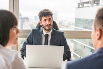 Male manager talking to businesspeople at workplace