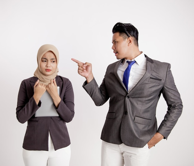 男性のマネージャーは、間違いを犯したことで女性のスタッフに腹を立てていました。仕事のオフィスの概念は、白い背景を分離しました