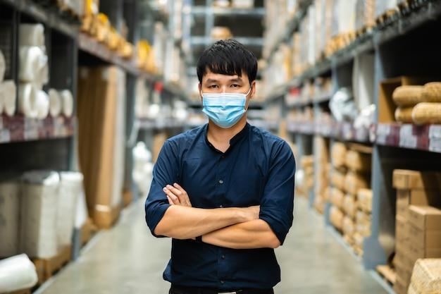 코로나 바이러스 전염병 동안 창고 상점에서 팔로 의료 마스크를 착용 한 남성 관리자가 넘어 프리미엄 사진