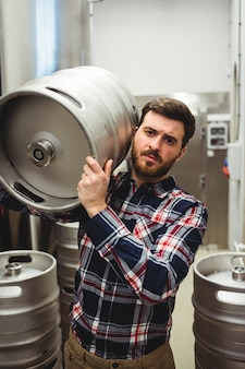 Male manufacturer carrying keg in brewery