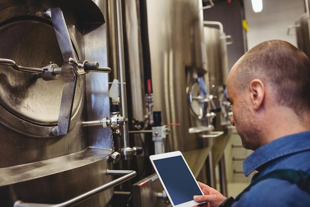 機械でデジタルタブレットを使用する男性メーカー