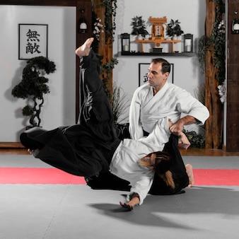 Istruttore di arti marziali maschio e tirocinante femminile nella sala pratica