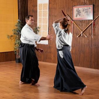 男性の武道インストラクターが女性の研修生と一緒に練習場でトレーニング