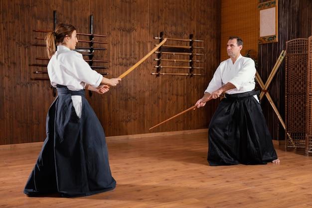 若い女性の訓練生と一緒に練習場で訓練する男性の武道のインストラクター