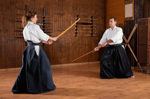 Male martial arts instructor training in the practice hall with young female trainee