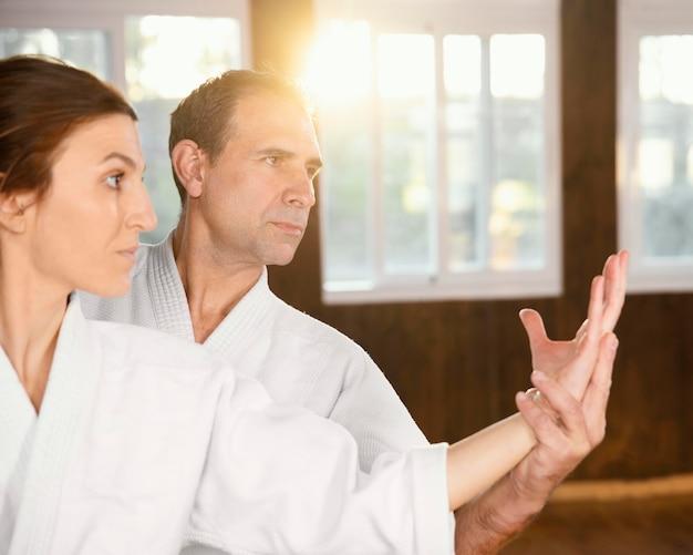 Istruttore di arti marziali maschile che si allena con tirocinante femminile nella sala pratica con spazio di copia