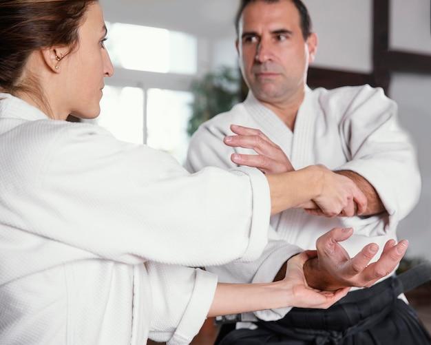 Istruttore di arti marziali maschio che si allena con tirocinante femminile nella sala pratica