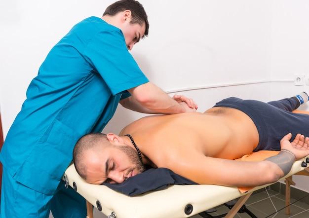 Мужской массажист делает массаж спины мужчине