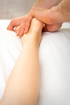 Male massage therapist massaging foot of young woman in spa beauty salon