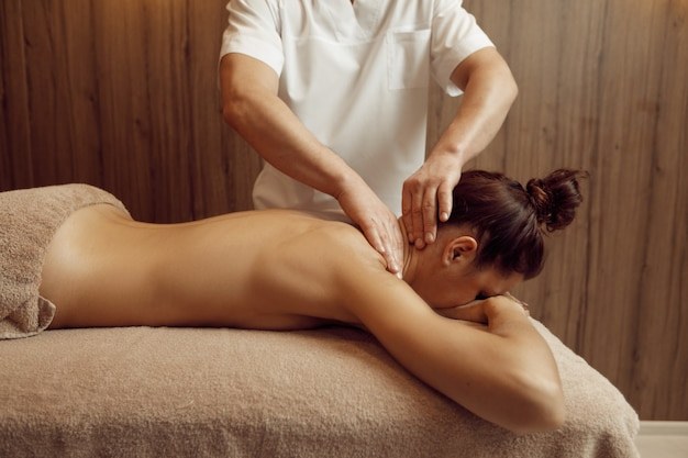 Male masseur  hands pampering neck to young woman in towel, professional massage. massaging and relaxation, body and skin care. attractive lady in spa salon