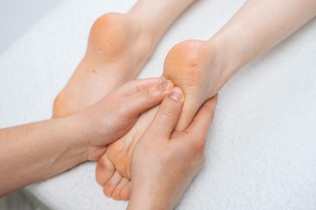 Мужской массажист массирует ноги молодой расслабляющей женщине, лежащей на массажном столе крупным планом