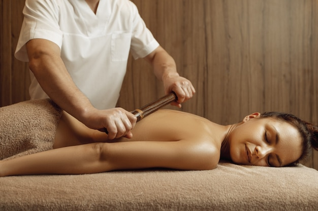 Male masseur pampering back by stick to young woman in towel, professional massage. massaging and relaxation, body and skin care. attractive lady in the spa salon