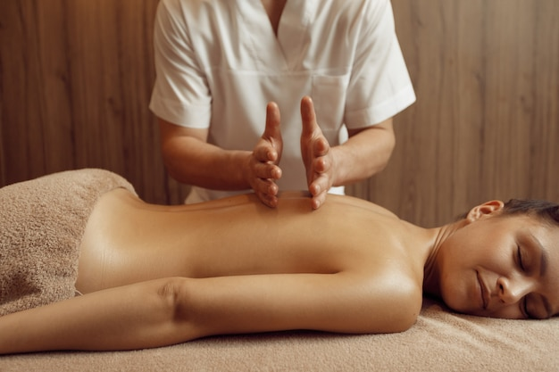 Male masseur pampering back to young woman in towel, professional massage. massaging and relaxation, body and skin care. attractive lady in spa salon