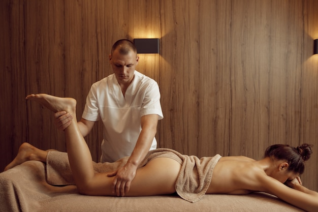 男性マッサージ師がタオルで若い女性に足を甘やかす、プロのマッサージ。マッサージとリラクゼーション療法、ボディケアとスキンケア。スパサロンで魅力的な女性