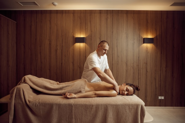 Male masseur pampering neck to young woman in towel, professional massage. massaging and relaxation, body and skin care. attractive lady in spa salon