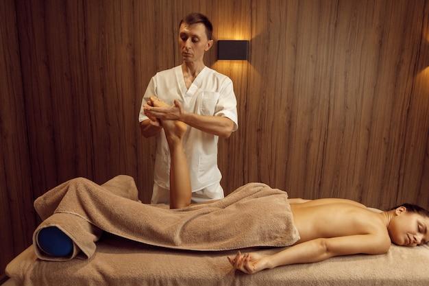 タオル、プロのマッサージで若い女性に足を伸ばす男性マッサージ師。マッサージとリラクゼーション療法、ボディケアとスキンケア。スパサロンで魅力的な女性