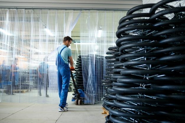 남성 정비공은 공장에서 카트에 자전거 바퀴를 운반합니다. 작업장의 자전거 림 조립 라인, 사이클 부품 설치, 현대 기술