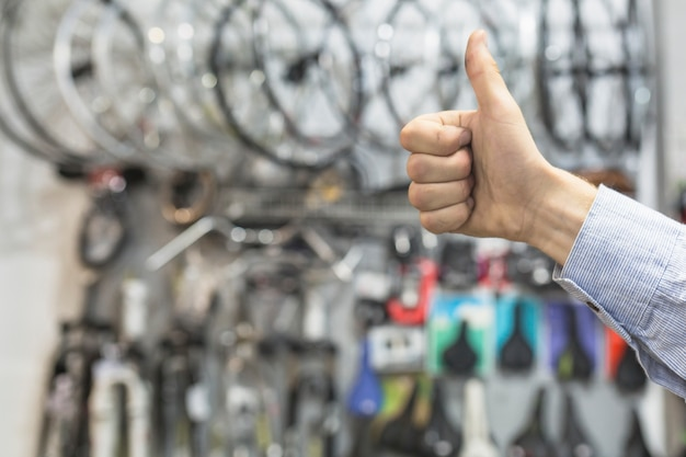 Male mechanic gesturing thumbs up in bicycle workshop