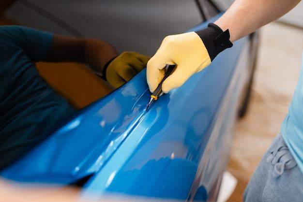 男性の整備士の手は、車両のドアに保護用のビニールホイルまたはフィルムを取り付けます。労働者は自動詳細を作成します