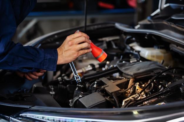 Мужской механик держит и сияющий фонарик для проверки проблемы двигателя автомобиля