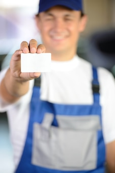 Male mechanic holding a business card in front of him.