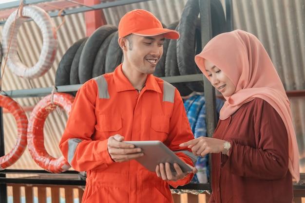 ウェアパックのユニフォームを着た男性の整備士と、スペアパーツのワークショップでカタログを表示するためにデジタルタブレットを使用している女性の顧客