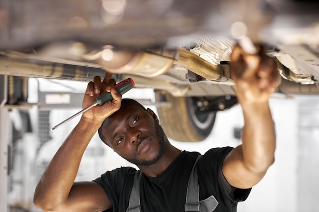 Male mechanic is working on a vehicle in a car service