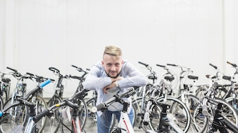 Male mechanic leaning on bicycle in workshop