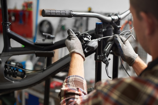 Male mechanic making service in bicycle repair shop using tools
