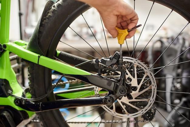 도구를 사용하여 자전거 수리점에서 서비스를 만드는 남성 정비사