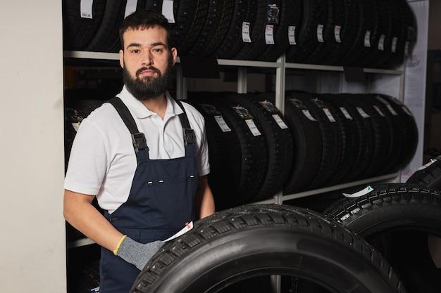 자동차 매장에서 자동차 타이어가 달린 랙 근처의 남성 정비공, 카메라를보고 선택을 돕고 고객과 고객에게 서비스를 제공하고 유니폼을 입고