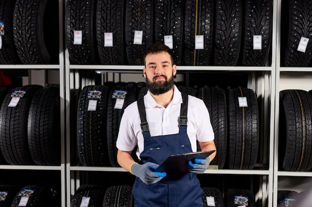自動車店で車のタイヤを持ったラックの近くの男性整備士、カメラを見て、選択を支援する準備ができて、顧客とクライアントにサービスを提供し、制服を着ています