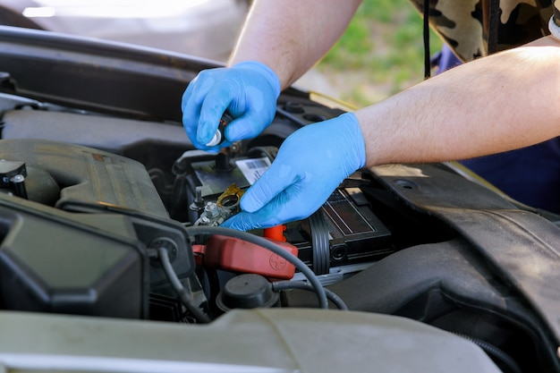 Male mechanic replacement car battery in workshop