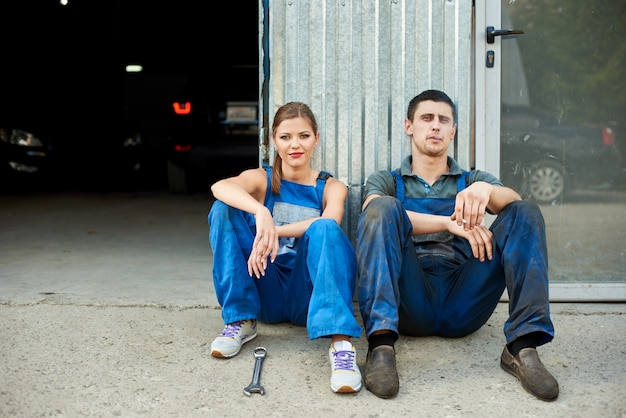 Male mechanic sits near garage and smokes a cigarette, young female mechanic sits by his side.