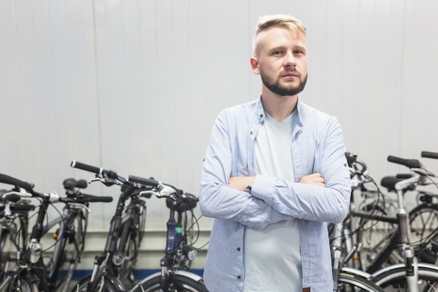 Male mechanic standing in front of bicycle