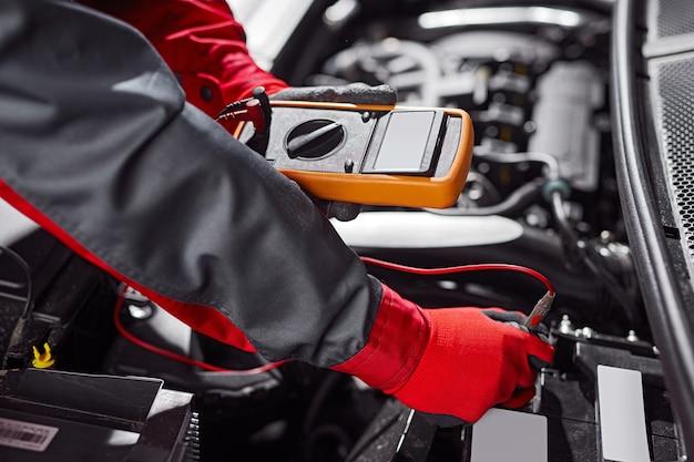 Мужской механик-тестер при диагностике аккумуляторной батареи автомобиля Premium Фотографии