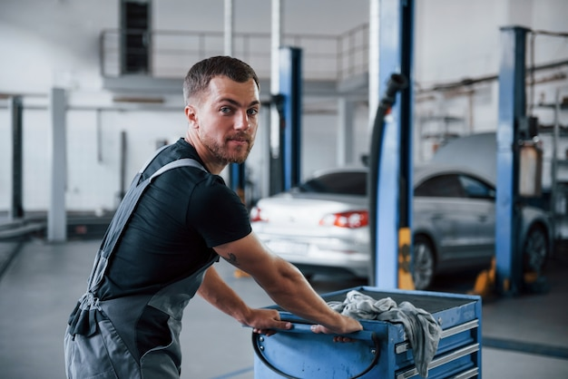 Male mechanic use different tools to repair broken automobile in garage.