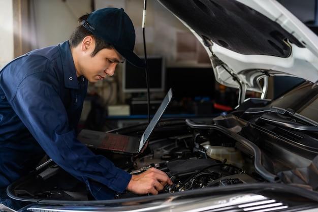 オートサービスで車を修理しながらラップトップを使用して男性メカニック