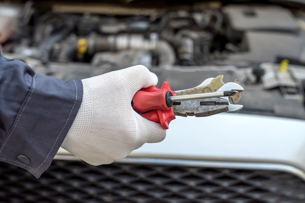Male mechanic using wrench key checking engine of car. auto service