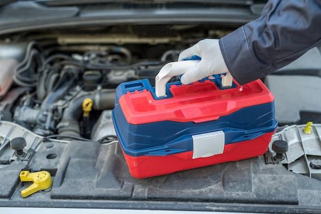 車のレンチキーチェックエンジンを使用する男性整備士。オートサービス