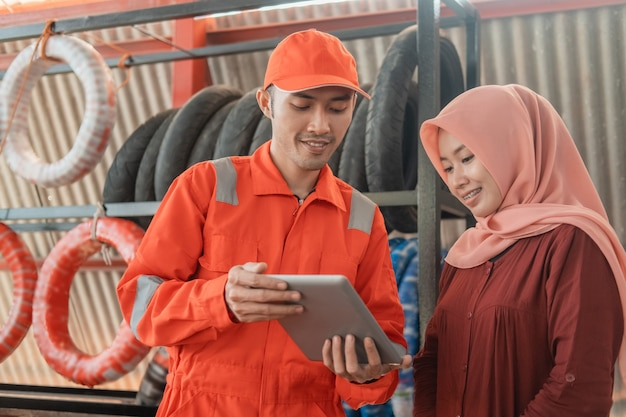 A male mechanic in a wearpack uniform and a female customer in a veil using a digital tablet to view the catalog at a spare part workshop